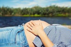 Zukünftige Mutter, die ihren schwangeren Bauch tappt Stockbild