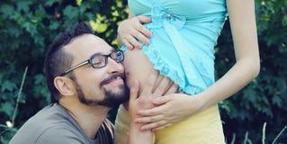 Zukünftiger hörender Vati der Bauch seiner schwangeren Frau. Stockfoto
