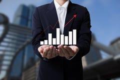 Zukunft des Finanzgeschäftskonzeptes, Geschäftsmann mit den kommenden Finanzsymbolen und den Stadthintergründen Stockfotos