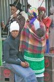 Zulu- byinvånare, en kvinna och behandla som ett barn och män som använder telefoner, möte i stadmitten, Sydafrika Royaltyfria Foton