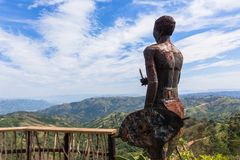 Zulu Statue Thousand Hills Landscape. Zulu metal statue rear overlooking viewpoint tribal homes over thousand hills and valleys of Inanda KZ-Natal South-Africa stock images
