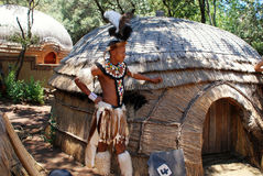Zulu warrior man , South Africa. LESEDI VILLAGE, SOUTH AFRICA - JANUARY 1,2008: Zulu man wearing warrior dress near tribal straw house on January 01, 2008 in Stock Photo