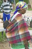 Zulu woman with child on her back dressed in brightly colored clothing, Zululand, South Africa Stock Photography