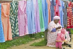 Zulu woman sewing garment in front of brightly colored dresses on display in Zulu village in Zululand, South Africa Stock Photography