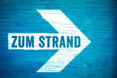 Zum Strand in German language, To the Beach text sign written on a white directional arrow on a blue wooden signboard. Concept for hot summer, tropical beach Royalty Free Stock Photography