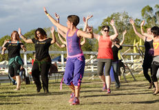 Zumba dancing instructor with smiling dancing people. A large group of very excited, happy and smiling people join in for free lessons from professional Zumba Stock Image
