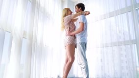 Zumba dentro dos pares de amor nos pijamas que abraçam perto da janela curtained grande