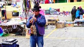 Zumbahua, Cotopaxi Ecuador, hombre de 040519 A que toca la flauta en un mercado callejero, metrajes