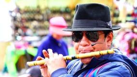 Zumbahua, Cotopaxi Ecuador, hombre de 040519 A que toca la flauta en un mercado callejero, almacen de video