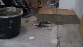 zumbe dentro o homem endireita a telha na superfície do cimento com engrenagem do laser filme