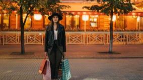 Zumbe dentro o tempo-lapso da menina bonita na roupa na moda que está com os sacos de compras na rua movimentada e que olha a câm video estoque