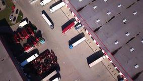 Zumbe dentro o tiro aéreo da área de carga industrial da construção de armazenamento do armazém onde muitos caminhões estão carre video estoque