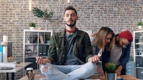 Zumbe para fora o tempo-lapso do empresário que relaxa no trabalho na posição dos lótus sobre a mesa