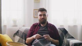 Zumbem dentro do homem sentar-se no sofá e fazer malha em casa