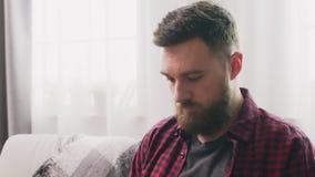 Zumbem dentro do homem sentar-se no sofá e fazer malha em casa video estoque