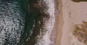 Zumbido aéreo da vista superior disparado para fora das ondas de oceano de formação de espuma bonitas que alcançam o Sandy Beach  vídeos de arquivo