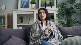 Zumbido-da jovem mulher que olha o filme policial assustador na tevê que senta-se no sofá em casa