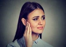 zumbido Femenino enfermo teniendo dolor de oído que toca su cabeza dolorosa imagen de archivo