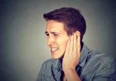 zumbido Hombre enfermo que tiene dolor de oído que toca su cabeza dolorosa imagen de archivo