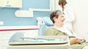 Zumi in considerazione del paziente femminile anziano che si siede nella sedia dentaria stock footage