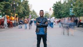 Zummi al rallentatore dei jeans d'uso e del bomber del tipo afroamericano felice che stanno da solo in via del centro stock footage