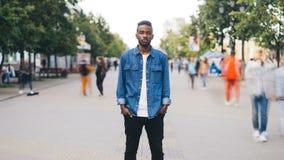 Zummi al rallentatore di singolo tipo afroamericano infelice che sta da solo nel centro urbano con le mani nei hockets e stock footage