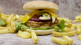 Zummi da sfuocato sugli hamburger fatti domestici deliziosi accanto alle patate fritte che si trovano sul fondo di legno archivi video