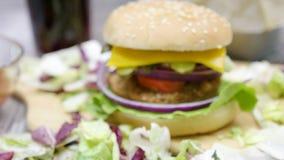 Zummi da sfuocato sull'hamburger con le fritture sulla tavola di legno stock footage