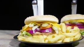 Zummi da sfuocato sull'hamburger fatto domestico con le fritture sulla tavola di legno sopra fondo nero video d archivio