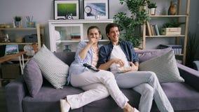 Zummi della commedia di sorveglianza delle coppie allegre sulla TV che ride mangiando il popcorn a casa archivi video
