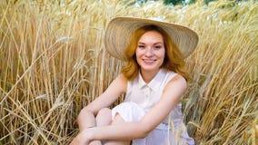 Zummi di giovane donna dai capelli rossi romantica che sorride alla macchina fotografica nel giacimento di grano archivi video