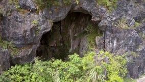 Zummi la caverna rocciosa con il lago dalla curva stradale fra la giungla archivi video