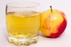 Zumo de Apple y de manzana en un vidrio imagenes de archivo
