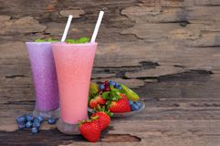 Zumo de fruta colorido de los smoothies de la fresa y del arándano, bebida sana el gusto delicioso en la comida de cristal de la  foto de archivo libre de regalías