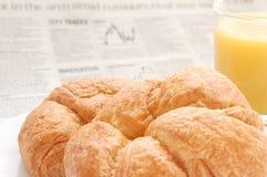 Zumo de fruta, croissant y documento comercial Fotografía de archivo libre de regalías