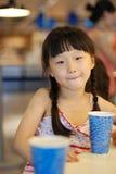 Zumo de fruta de consumición de la muchacha hermosa foto de archivo