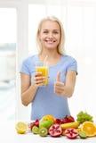 Zumo de fruta de la mujer y el mostrar pulgares de consumición para arriba foto de archivo