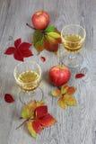 Zumo de manzana en un vidrio, una manzana roja y hojas de otoño Foto de archivo