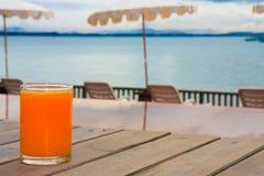 Zumo de naranja cerca del océano Imagenes de archivo