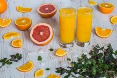 Zumo de naranja con hielo en vidrios cerca de la fruta cítrica y de la menta en el fondo de madera ligero Fotografía de archivo