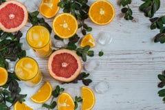 Zumo de naranja con hielo en vidrios cerca de la fruta cítrica y de la menta en el fondo de madera ligero Foto de archivo