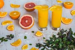 Zumo de naranja con hielo en vidrios cerca de la fruta cítrica y de la menta en el fondo de madera ligero Imágenes de archivo libres de regalías