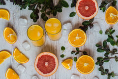 Zumo de naranja con hielo en vidrios cerca de la fruta cítrica y de la menta en el fondo de madera ligero Imagenes de archivo
