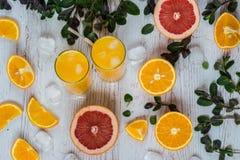 Zumo de naranja con hielo en vidrios cerca de la fruta cítrica y de la menta en el fondo de madera ligero Imagen de archivo libre de regalías