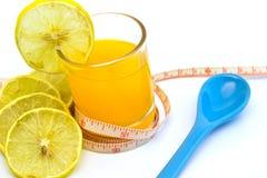 Zumo de naranja con la cinta métrica y la cuchara, aisladas en blanco Foto de archivo