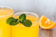 Zumo de naranja con la menta del primer en vidrios en el fondo ligero Fotografía de archivo