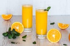 Zumo de naranja con la menta en vidrios en el fondo de madera ligero Imagen de archivo