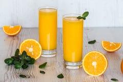 Zumo de naranja con la menta en vidrios en el fondo de madera ligero Fotografía de archivo libre de regalías