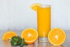 Zumo de naranja con la menta en vidrios en el fondo de madera ligero Foto de archivo