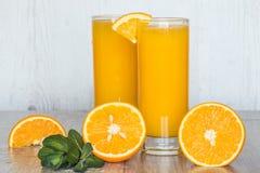 Zumo de naranja con la menta en vidrios en el fondo de madera ligero Fotos de archivo libres de regalías